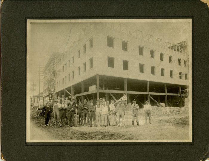Untitled photograph of construction workers in front of a downtown Portland Oregon construction site. OREGON - PORTLAND - CONSTRUCTION HISTORY.